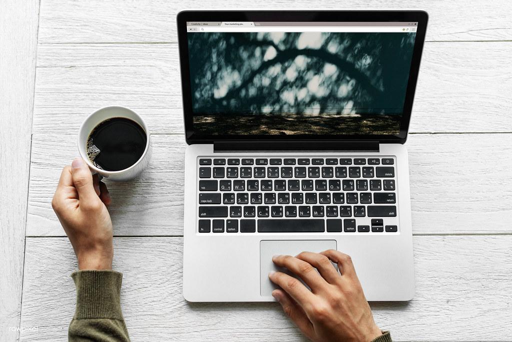 Človek používajúci notebook, ktorý je položený na stole.