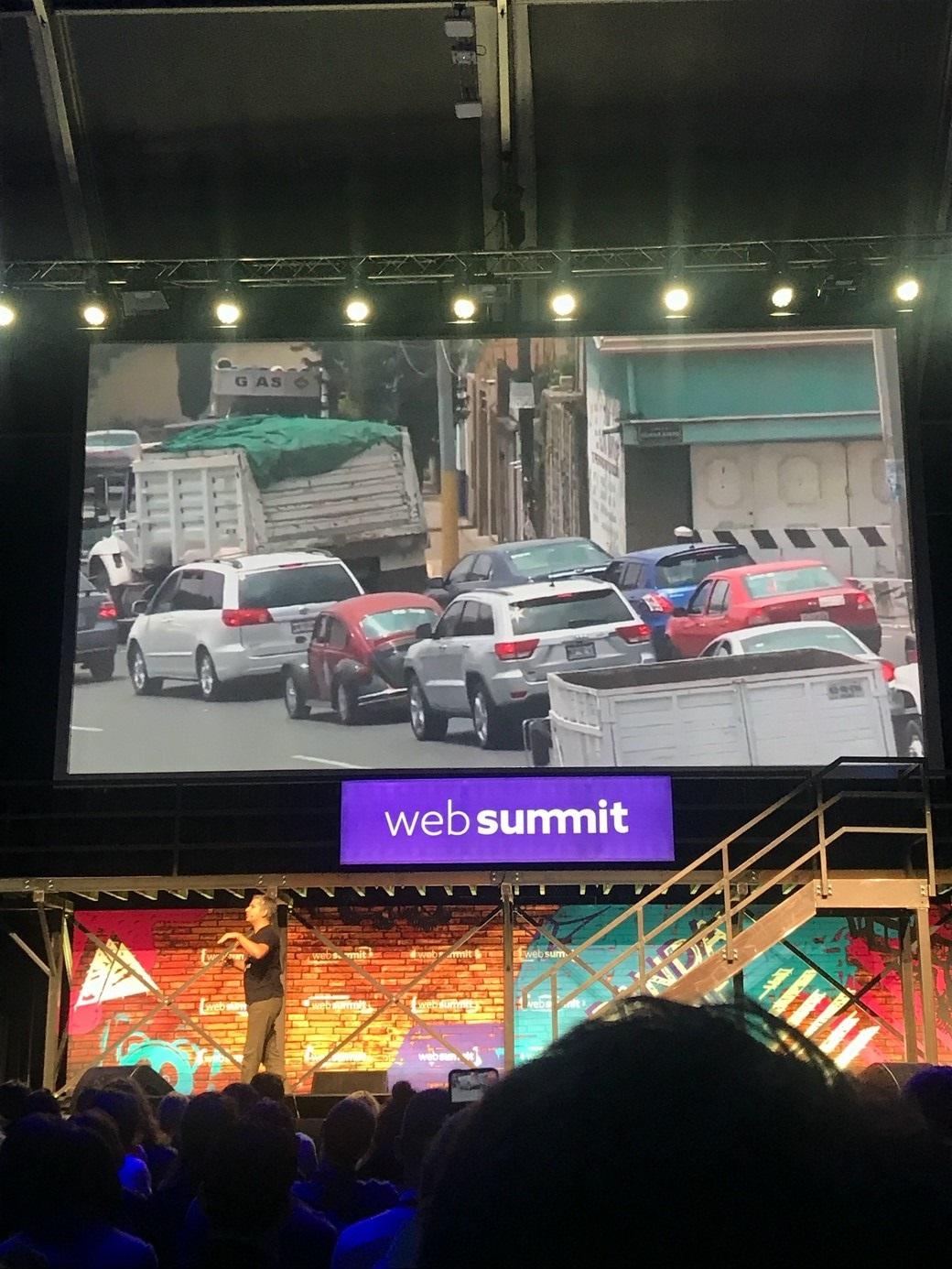 Muž stojaci pred obrazovkou prezentuje na Web Summite.