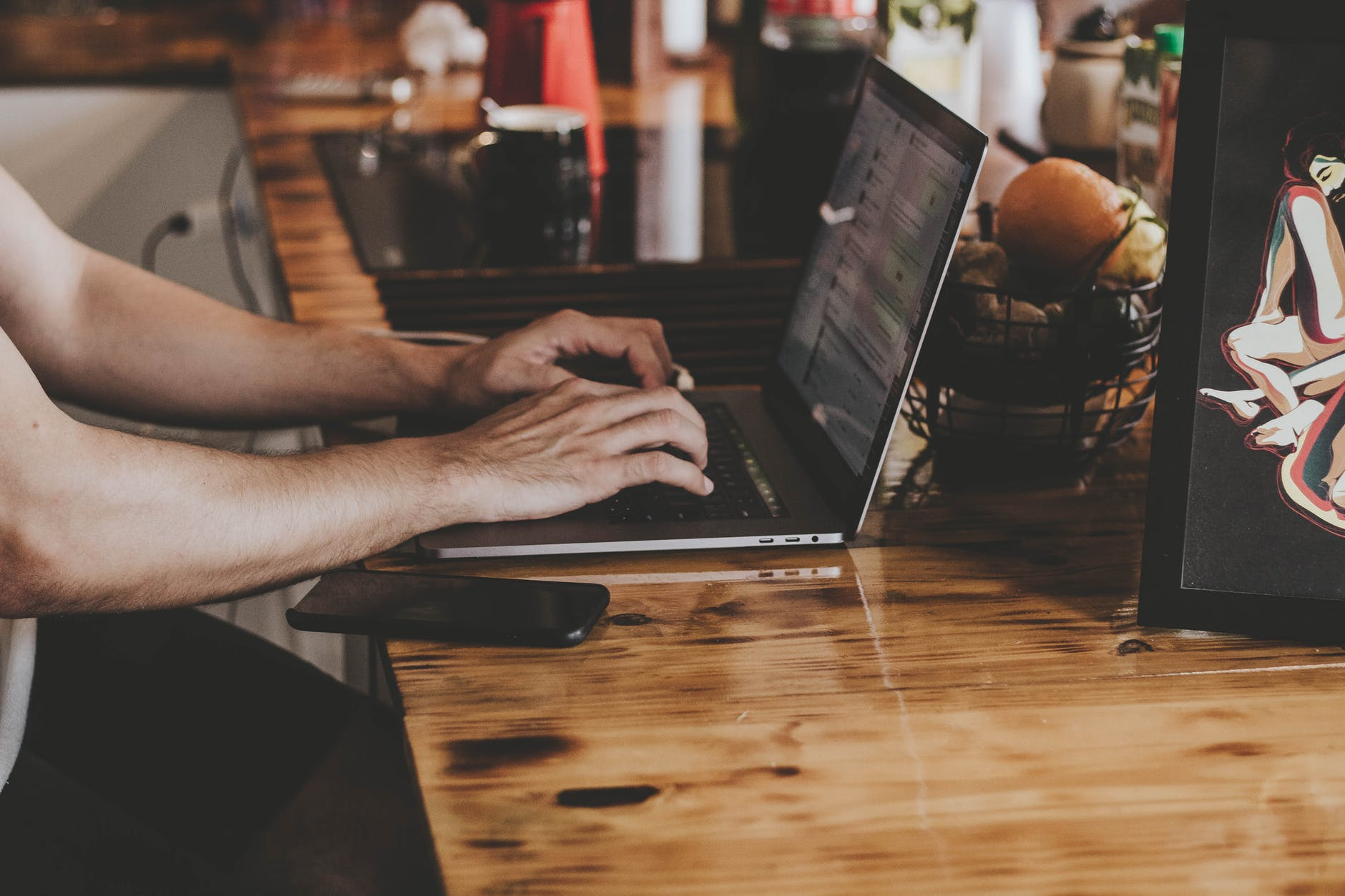 Muž používa notebook, ktorý je položený na stole.