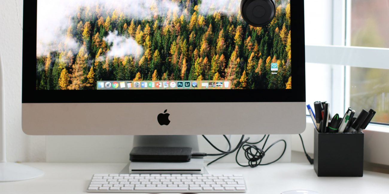 Pracovný stôl. na ktorom je obrazovka počítača s pozadím lesov.